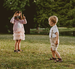 Cute little girl taking a phto of her younger brother