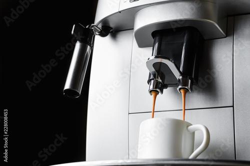 Modern coffee machine brews espresso coffee in white cup