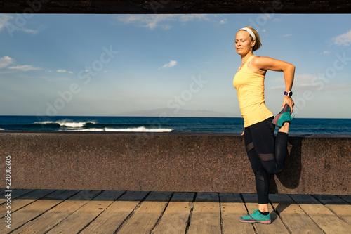 Kobieta biegacza rozciąganie przy nadmorski na pogodnym letnim dniu