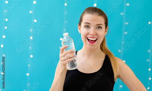 Młoda kobieta z bidonem na błyszczącym lekkim tle