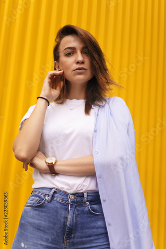 Foto Murales Portrait attractive woman on yellow background. she look on camera pretentious or arrogantly. Brunette girl with short hair.