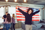 Guy with a beautiful smile with the flag of america indoors. Independence Day of the USA. - 228045259