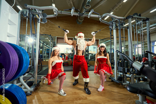 Sticker Sports Santa Claus with girls in Santa's costumes in the gym on Christmas and New Year.