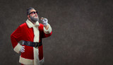 Santa Claus with a fashion hairdress smokes a cigar on the background of copyspace. - 228045820