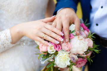 Hands of bride and groom on wedding bouquet. Marriage concept
