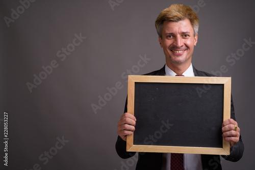 Biznesmen z blondynem przeciw popielatemu tłu
