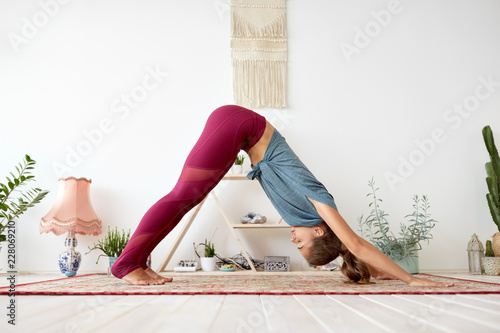fitness, sport and healthy lifestyle concept - woman doing yoga downward-facing dog pose on mat at studio
