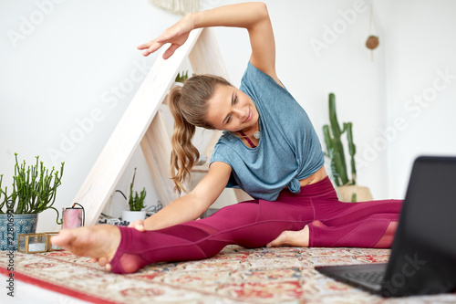 fitness, technology and healthy lifestyle concept - woman with laptop computer exercising at yoga studio