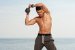 Portrait of young strong man training with kettle bell.