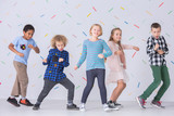 Girls and boys dancing together in the school. Happy friends against colorful wallpaper - 228074485