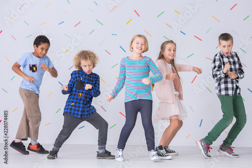 Girls and boys dancing together in the school. Happy friends against colorful wallpaper