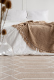 Patterned carpet in natural bedroom interior with brown blanket on white bed. Real photo - 228075662