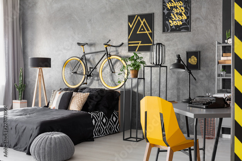 Foto Murales Posters and bike above black bed in grey teenager's room interior with pouf and yellow chair. Real photo