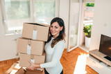 Smiling young woman moving to a new apartment. - 228105410