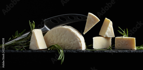 Sticker Sheep cheese with rosemary on a black background.