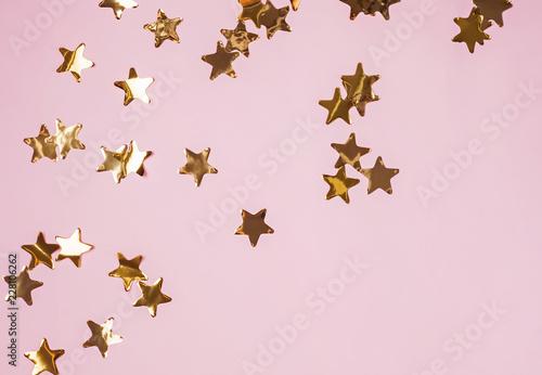 Złote błyszczące dekoracyjne gwiazdy na różowym tle, odgórny widok.