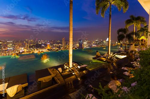 Leinwandbild Motiv Pool on roof and Singapore city skyline