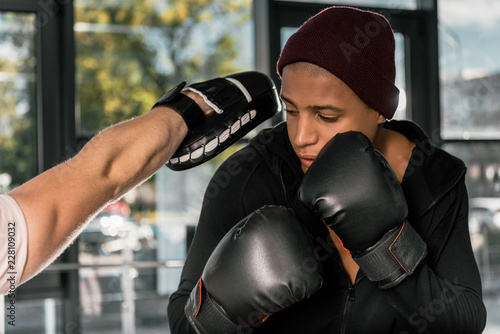 Poster selective focus of african american boxer in boxing gloves practicing with trainer at gym