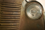 fragment of the front of a rusted vintage car, part of the radiator and headlight
