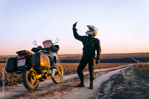 Motorbiker travelling, autumn day, motorcycle off road, rider, adventurer, extreme tourism, cold weather clothes, uses smartphone, internet, search, find, lost the signal