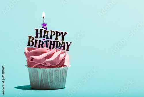 Leinwandbild Motiv Birthday muffin with candle on a blue background.