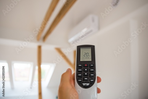 Man adjusting and regulating temperature on home air conditioner