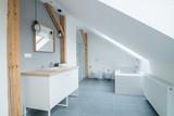 Bright modern bathroom with grey walls, mirror and bathtub. - 228114029