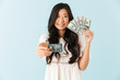 Happy asian beautiful woman isolated over blue background holding credit card and money.