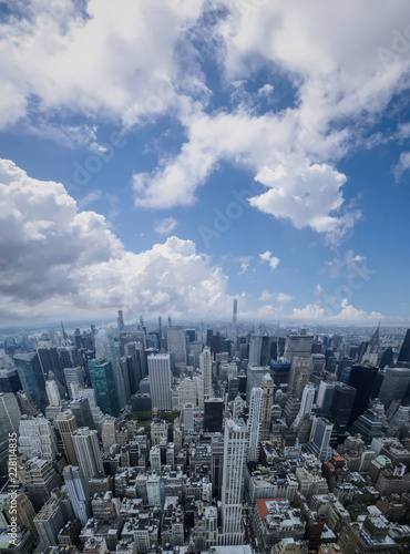 Aerial view of Manhattan skyscraper from Empire state building observation deck. Cloudy blue sky