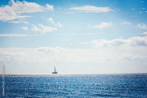 Sail boat on the sea at the horizon with blue water and cloudscape