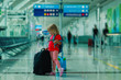 little girl with suitcases travel in airport, family vacation