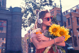 Bright sunflowers. Young stylish woman looking at bright yellow sunflowers while walking down the city center
