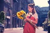 Nice bouquet. Dark-haired woman wearing bright red summer dress holding nice bouquet of bright sunflowers in her hands