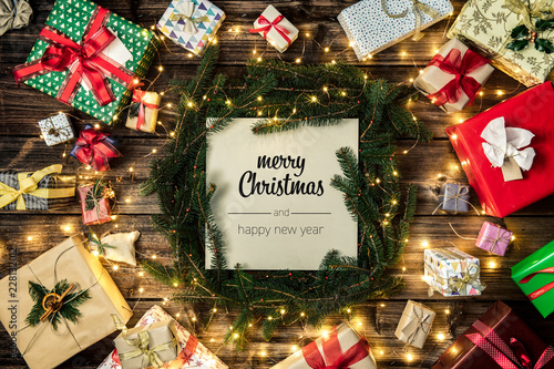 Merry Christmas and happy new year greetings in vertical top view vintage wood.Pine branches,ribbons, lights,gift present boxes decorated frame.Xmas winter holiday season social media card background