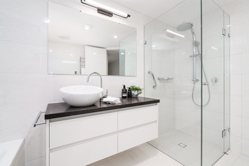 Large modern bathroom interior with floor to ceiling tiling and luxury fittings.