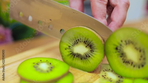 Women's hands Housewives cut with a knife fresh kiwi on the cutting Board of the kitchen table