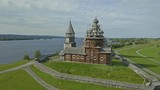Aerial revealing wide shot of Kizhi Island main church with green lawn, a stack of hay, farm, authentic old architecture, UNESCO - 228144630