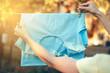 Leinwandbild Motiv Blue green T-shirt hanging on a clothespin female hand nature on blur background