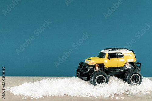 Foto Murales yellow SUV monster car truck toy in winter snow