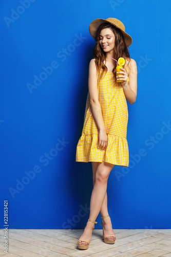 Young woman in yellow sarafan posing with cup fruit juice