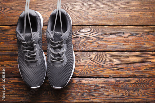 Foto Murales Gray sport shoes on wooden wall background