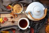 tea cup and a white teapot on a wooden table with spices and some autumn leaves, high angle view from above, selected focus - 228155669