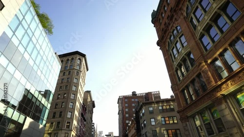Sunlight reflecting in glass buildings in Soho NYC New York City Manhattan street dolly moving shot