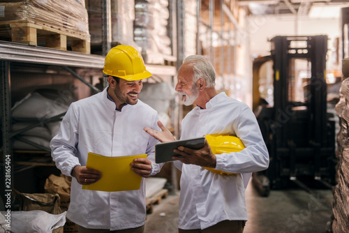 Team work. Picture of two man warehouse employes smiling and looking together at digital tablet. Older college is learning younger one how to solve a problem.Standing in big warehouse.