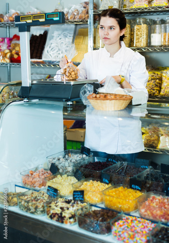Foto Murales Girl in uniform  selling candied fruits and nuts