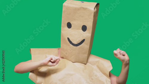 Leinwanddruck Bild concept of emotions, gestures. a man with paper bags on his head, with a painted emoticon, smile, joy