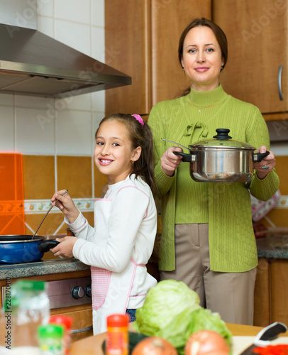 Poster Mother with daughter cooking at kitchen