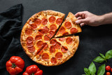 Hand picking slice of pepperoni pizza. Pizza party. Hot italian pepperoni pizza on black concrete background, top view