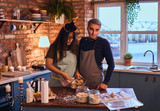 Attractive couple with makeup together cooking breakfast in loft style kitchen at morning. - 228172843