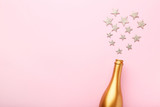 Decorated champagne bottle with stars on pink background - 228177839